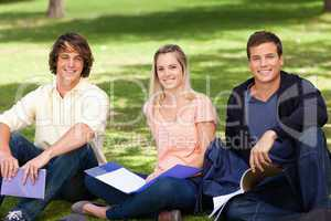 Portrait of three students in a park