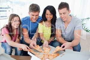 friends grabbing some pizza as they look at the box