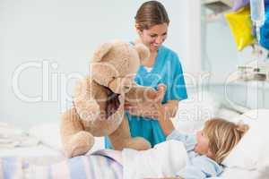 Nurse showing a teddy bear to a child
