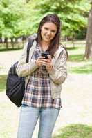 Young smiling student using a smartphone