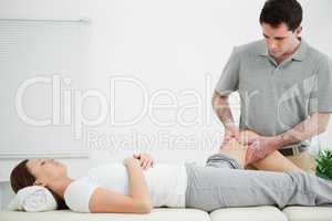 Physiotherapist massaging the leg of a woman while standing