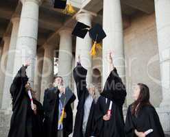 Smiling graduates throwing their hats in the sky
