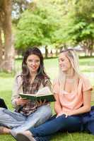 Two teenagers sitting with a textbook