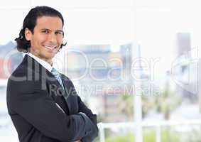 Executive standing upright in front of a window and looking towa