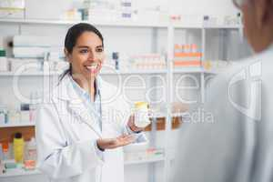 Smiling pharmacist holding a drug box