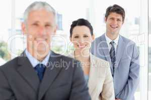 Young smiling executive following two business people