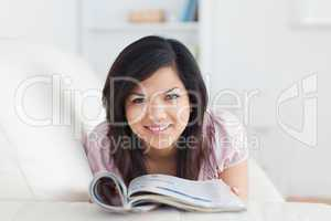 Woman resting on a sofa while holding a magazine