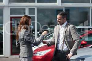 Businesswoman giving car keys to a man