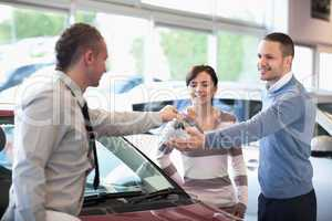 Smiling couple receiving keys from a car dealer