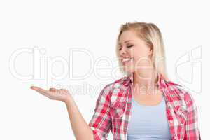 Smiling woman putting her hand palm up while standing