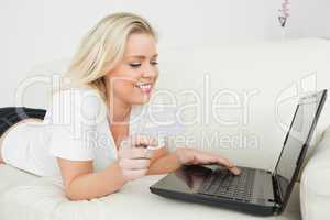 Woman looking at a laptop and holding a credit card