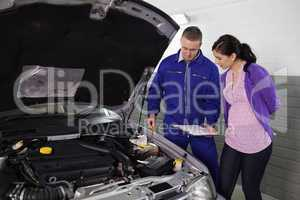 Mechanic showing a par of the engine to a woman
