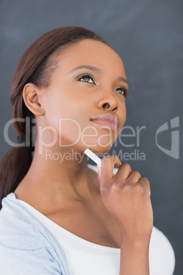 Black woman looking up while holding a chalk