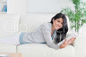 Woman holding a magazine while relaxing on a couch