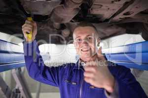 Smiling man repairing a car with his thumb up