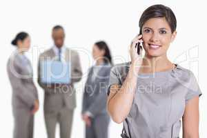 Close-up of a woman smiling on the phone and co-workers with a l