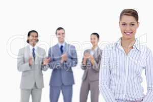 Close-up of a woman smiling with business people applauding