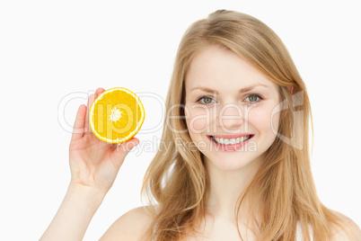 Joyful woman presenting an orange