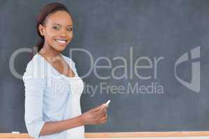 Black woman holding a chalk next to a blackboard