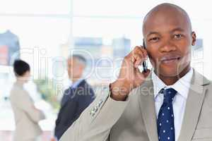 Serious businessman in a suit talking on the phone while his tea