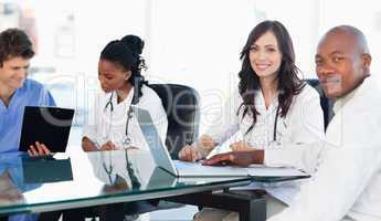 Two members of a medical team looking at the camera while workin