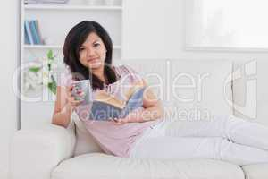 Woman lying on a couch while holding a mug and a book