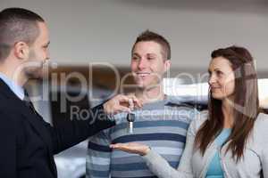 Businessman giving car keys to a woman