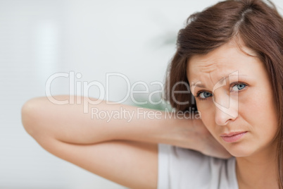 Brown-haired girl placing her hand on her neck