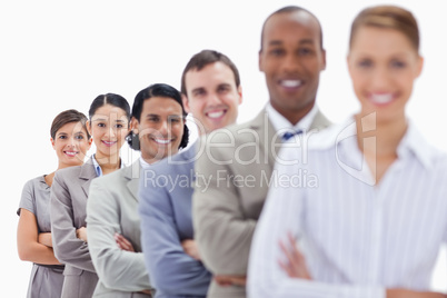 Close-up of smiling workmates dressed in suits crossing their ar