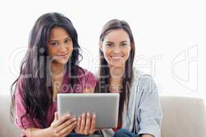 Two ladies with a tablet pc in hand looking at the camera