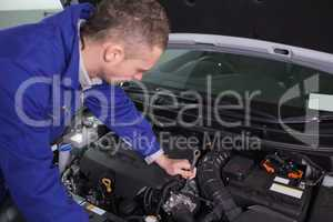 Mechanic repairing the engine with a spanner