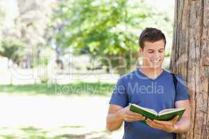 Muscled student holding a textbook