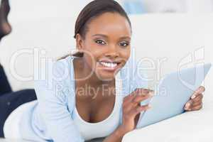 Black woman smiling while holding a tablet computer