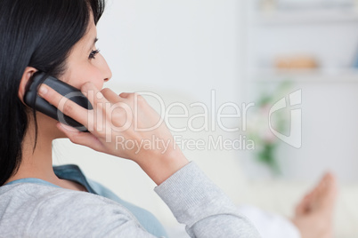 Woman lying on a couch and phoning