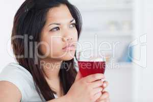 Thinking woman holding a glass of red wine