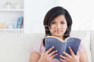 Woman sitting on a couch and holding a book