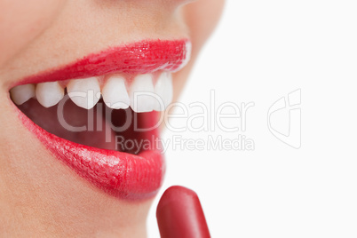 Happy woman putting lipstick on her lips