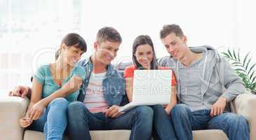 A smiling group of friends watching a show on the laptop togethe