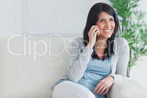 Woman talking on the phone while relaxing on a couch
