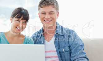 A couple with a laptop sitting as they smile and look into the c