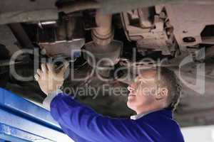Mechanic repairing the below of a car
