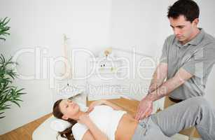 Osteopath touching the hip of a woman with his fingertips