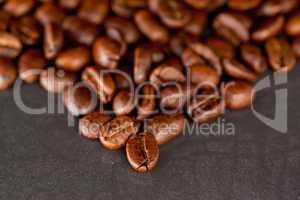 Blurred coffee seeds laid out together on a black table
