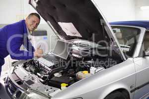 Mechanic leaning on a car engine