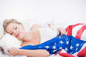 Blonde woman sleeping with a US flag