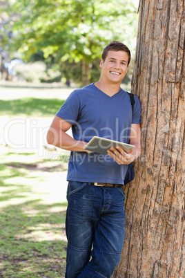 Portrait of a student leaning against a tree while using a touch