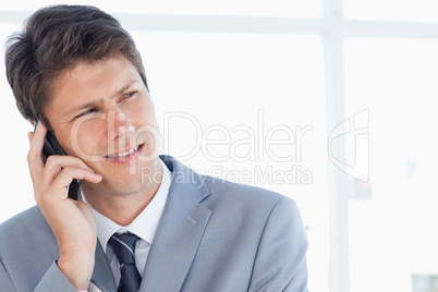 Stern businessman talking on the phone while looking towards the