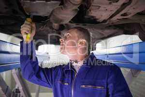 Man looking at the below of a car while repairing