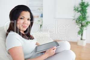 Woman sitting on a sofa while holding a tactile tablet