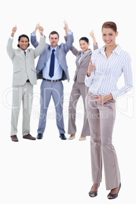 Secretary in foreground and business people with their thumbs up